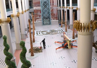 Workers repair palm tree fronds in the Center Court area as part of renovations currently in progress at the Metrocenter Mall in Jackson.
