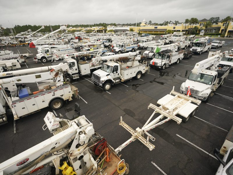 Utility trucks stage in a parking lot as they prepare to repair damage to the power grid caused by Hurricane Ida, Monday, Aug. 30, 2021, in Gulfport, Miss. (AP Photo/Steve Helber)