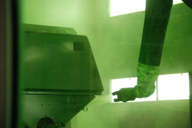 A robotic arm applying the trademarked John Deere paint
