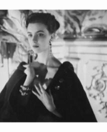 Illaria Occhini wearing long earrings and a sark cape