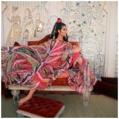 ca. 1967, Udaipur, India --- Model Simone D'Aillencourt posed inside the Lake Palace in Udaipur, in a swirled flame-print poncho and jewel-cuffed pants by Emilio Pucci. --- Image by � Cond� Nast Archive/Corbis
