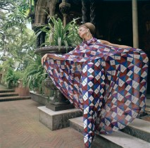 ca. 1965 --- Model posing outside wearing evening dress by Galanos in harlequin printed silk of blue, red, white, and pink with matching over sheath. --- Image by © Condé Nast Archive/CORBIS