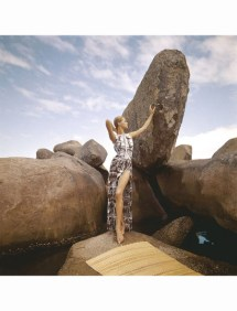 Model posing at beach on large rocks wearing Galitzine maillot in white with brown print and matching skirt in the reverse pattern with deep side slit. *** Local Caption *** Veruschka;