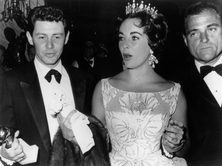 1958: American singer Eddie Fisher standing with British-born actor Elizabeth Taylor and her third husband, producer Mike Todd, at the Golden Globe awards, California. Fisher is holding his award for Best TV show for his program, 'Coke Time.' In March of that year, Todd was killed in a plane crash, and a year later Taylor married Fisher. (Photo by Hulton Archive/Getty Images)