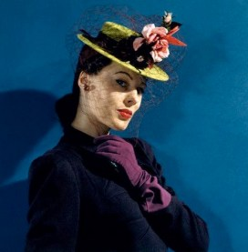 Meg Mundy in chartreuse felt hat with roses and hummingbirds, purple gloves, and purple veil and ribbons Vogue 1941