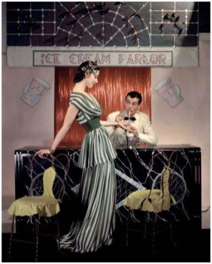 Model wearing lime-green-and-white silk chiffon summer dress with low-draped cowl and soft tunic, serving man in a dinner jacket at an ice cream parlor 1941