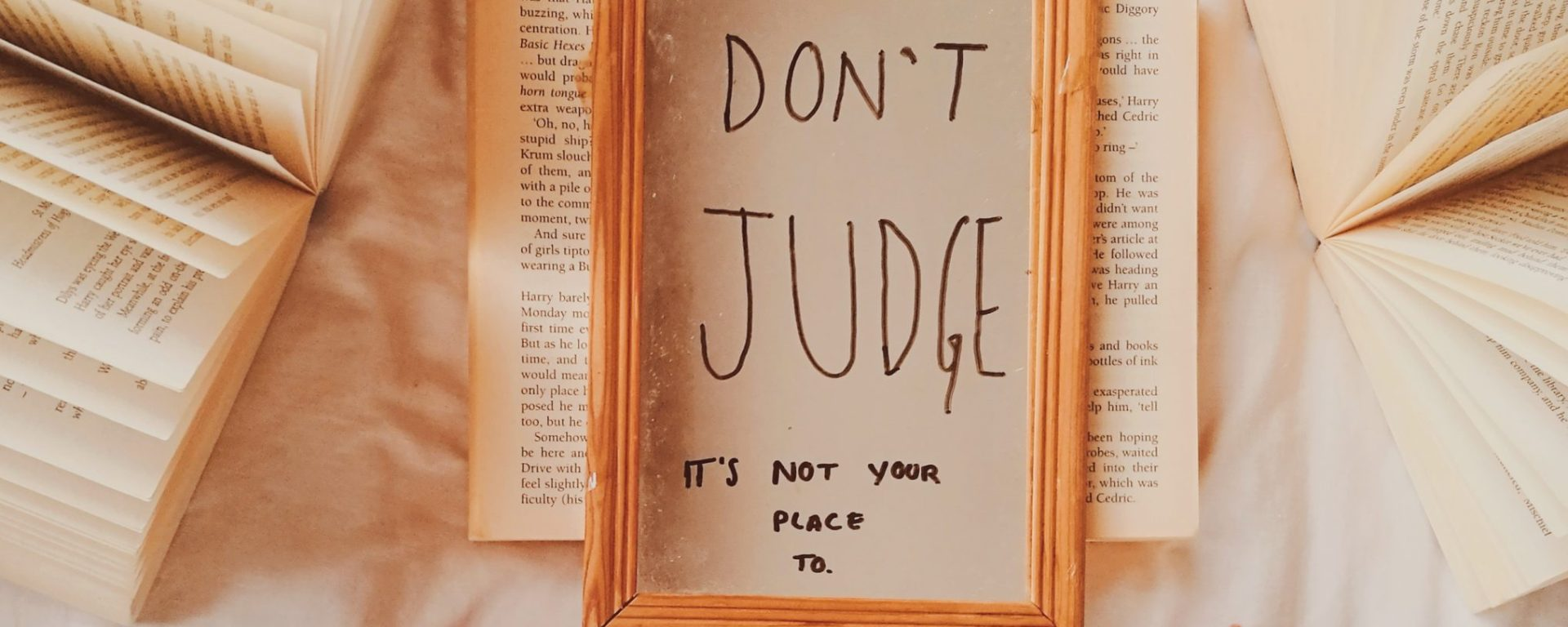 a mirror with the words dont judge along with some books and a laptop for the post social media: behind the screens