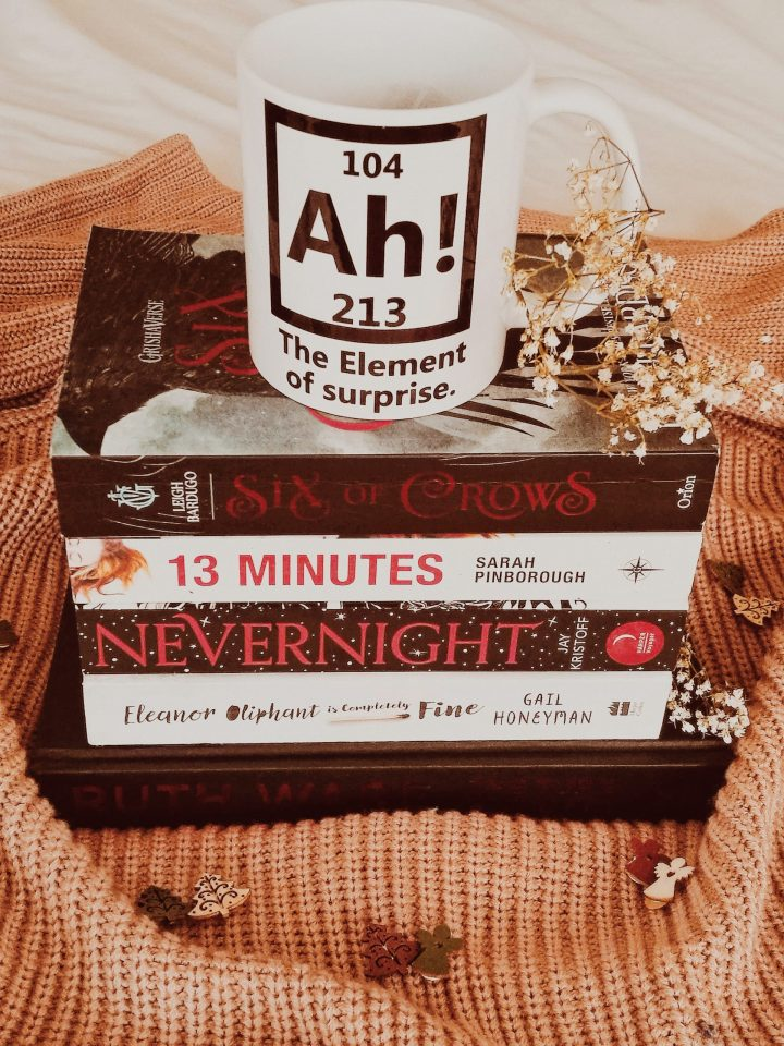 stack of red and white books and a mug, ah the element of surprise for blogmas post bookish and blog new years resolutions