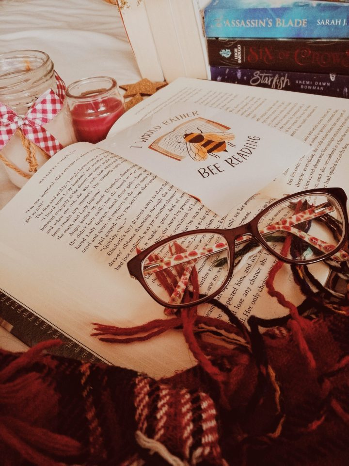 cosy candles, books, and glasses for blogmas post self care winter pamper night in with postcard i would rather bee reading
