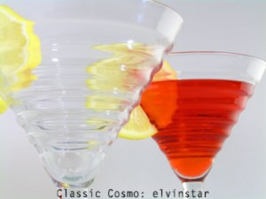 one empty cocktail glass with lemon and one full with red liquid and lemon