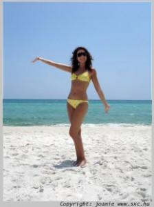 woman on a beach in a yellow bikini