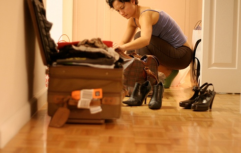 middle aged woman packing, woman packing, shoes, suitcase
