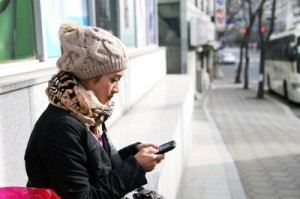 girl on cell phone, wearing a beeney and black leather jacket with a scarf, sitting on a bus stop