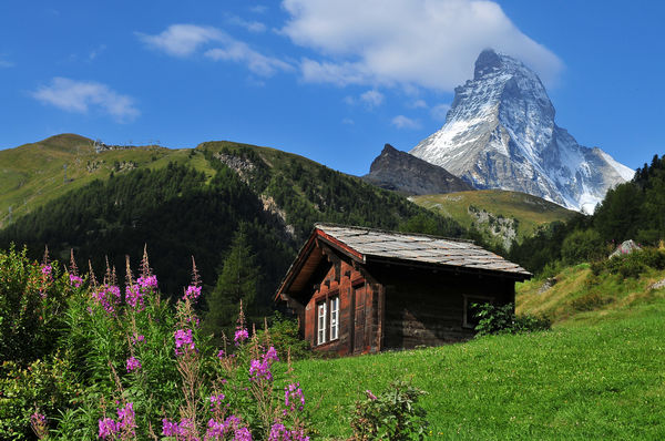 zermatt, ski getaway, sunny landscape at the base of the mountain with a lone house