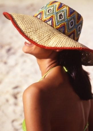 woman in a straw hat tanning on a sunny beach