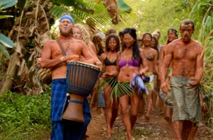 a group of people wearing tribal clothes in a tropical forest