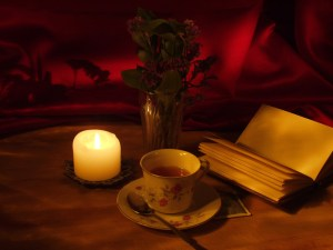 Book with cup of tea and candle