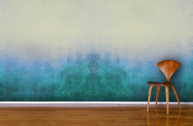 A wooden chair against a blue grunge mural.