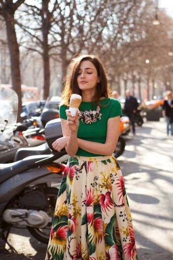 Bold printed skirt paired with a green T-shirt and chunky necklace.