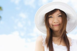 Young woman smiling wearing white sunhat