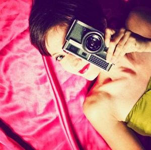 girl laying down holding a camera to her eye