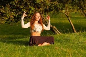 woman meditating in a field