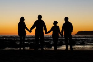 Family holding hands on beach discussing life insurance
