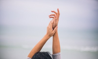 woman reaching hands up