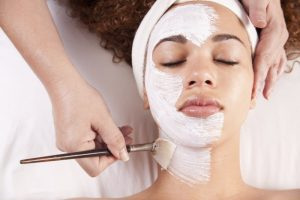woman getting face mask at spa