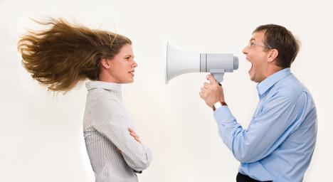 man speaking to woman through megaphone
