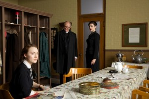 """Saoirse Ronan as """"Eilis,"""" Jim Broadbent as """"Father Flood"""" and Jessica Paré """"Miss Fortini"""" in BROOKLYN. Photo by Kerry Brown. © 2015 Twentieth Century Fox Film Corporation All Rights Reserved"""