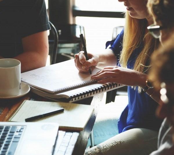 woman writing on pad at coffee meeting
