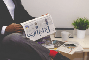 man reading a business newspaper to impress your boss
