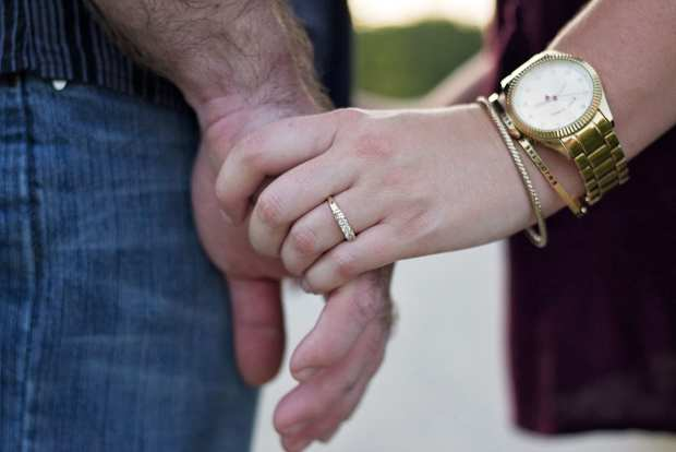 couple holding hands showing off engagement ring alternatives