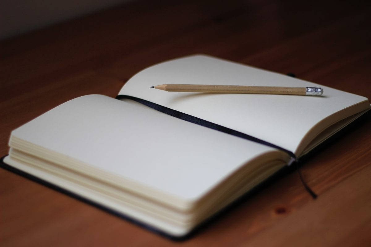 pencil and blank journal on table