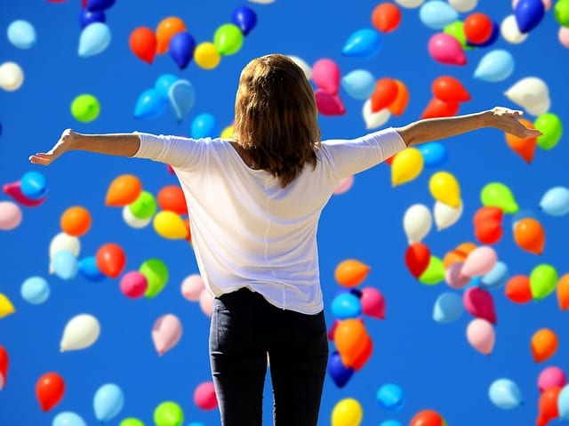woman spreading her arms in front of ballons