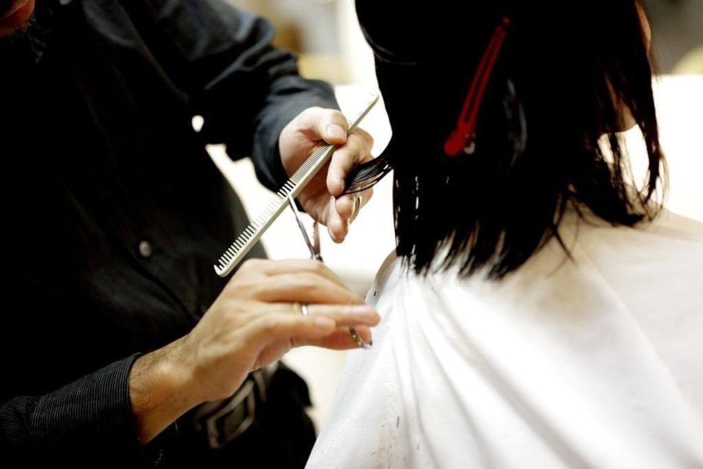 man cutting woman's hair