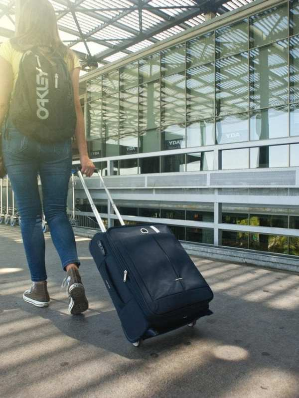 woman at airport pulling rolling suitcase