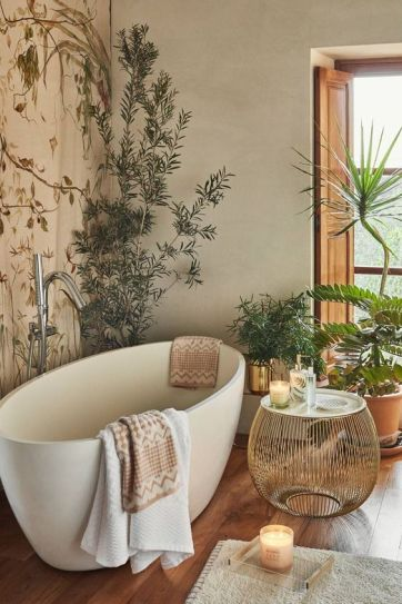 Bathroom ideas and accessories on a budget. Perfect combination of green plants modern bathtub and rattan accessories