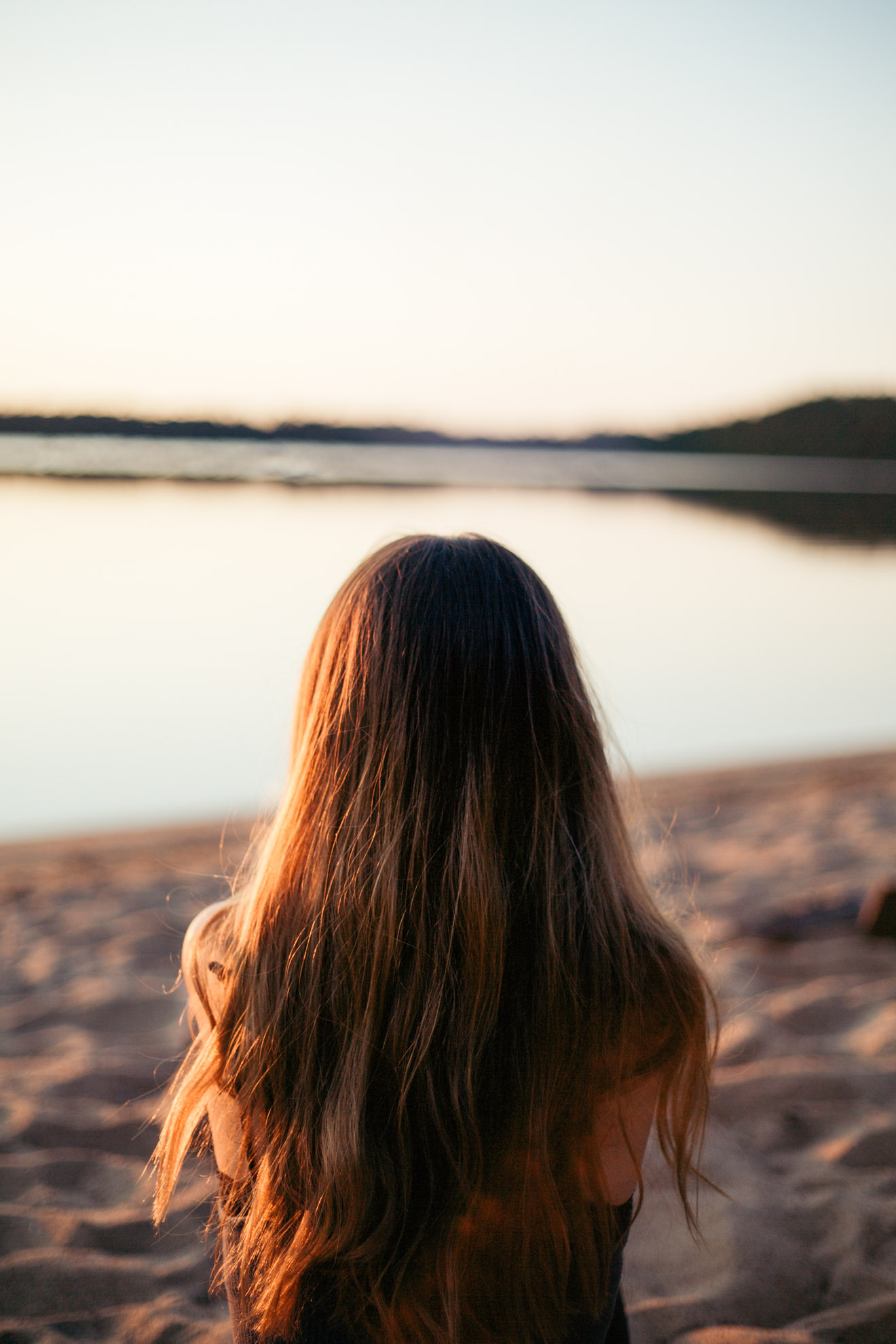 girl sitting on beach in wisconsin at sunset