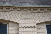 decorative dentil work around top perimeter and between recessed window opening