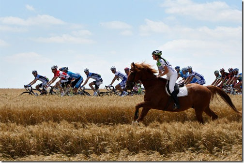 CHOLET, FRANCE - JULY 09:  A woman on a horse runs alongside the peloton during stage five of the 2008 Tour de France from Cholet to Chateauroux on July 9, 2008 in Chateauroux, France.  (Photo by Jasper Juinen/Getty Images)