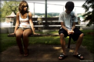 young couple sitting apart on bench