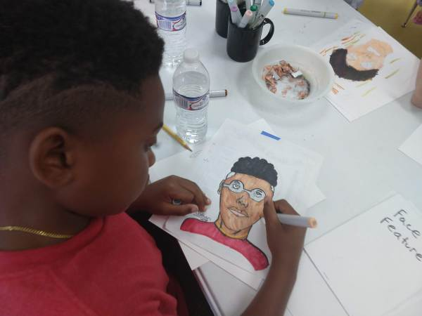 Boy drawing a self portrait