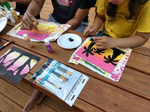 Teens painting sunset landscapes