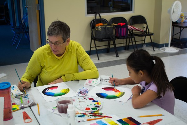 Woman and girl painting color wheels
