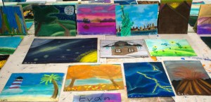 Many chalk pastel drawings laid out on a table for display