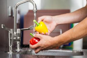 Kitchen porter washing pepper under running tap in professional kitchen
