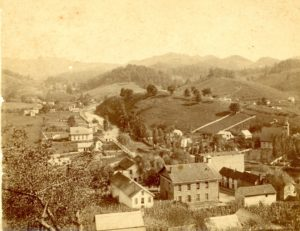 "Bakersville, probably in the late summer of 1899 or 1900. The Baptist church is on the left, the Methodist church on right. The 1868 Mitchell County Courthouse is in the foreground. There is a wooden sidewalk up ""Water Street."""