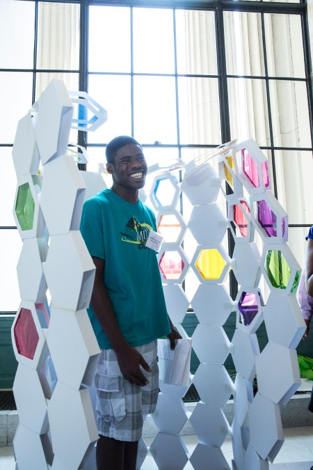 """Engineering Design program student Jeremiah Akinsulire of Jamaica, NY steps into """"The Busy Bee,"""" a model phone booth made by Architecture program students Jennah Jones of Chapel Hill, NC, Carlos Romero of Boston, MA, Emanuel Perez of Chicago, IL and Diondra Dilworth of Las Vegas, NV."""